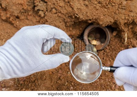 Ancient Coins And Magnifier.the Concept Of The Discovery Of Ancient Treasures.