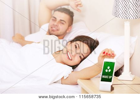Young couple waking up with mobile alarm clock