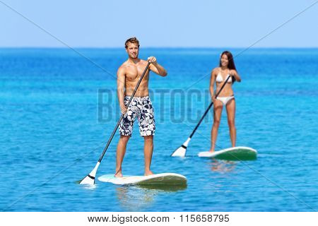 Man and woman stand up paddleboarding on ocean. Young couple are doing watersport on sea. Male and female tourists are in swimwear during summer vacation.