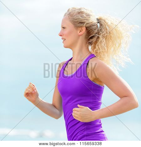 Determined young woman runner  jogging at beach. Fit blond female running is wearing purple tank top. Jogger is exercising during summer.