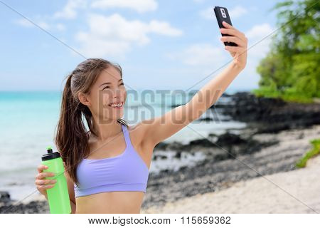 Smiling sporty woman taking selfie using smartphone on beach. Beautiful fit fitness female in sports bra is holding water bottle. Attractive young woman is posing at sea shore.