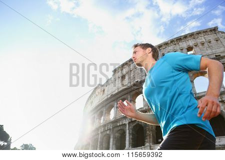 Running male runner jogging against Colosseum. Man athlete  on run confident in sportswear. Young man is exercising on sunny day living healthy active lifestyle in Rome, Italy.