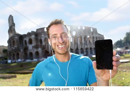 Happy young jogger showing smartphone with blank screen against Colosseum. Confident male runner is listening music on sunny day. The empty space on mobile phone can be used for advertisement purpose.