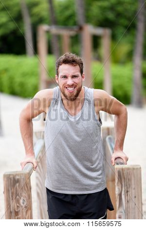 Man doing difficult strength training exercises - fitness cardio workout. Young Caucasian male athlete working out hard on outdoor jungle gym / monkey bars on summer beach