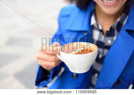 Hands closeup of woman drinking at cafe holding a coffee cup with a milk rosetta foam shape on top. Outdoor terrace at coffee shop or restaurant.