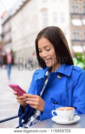 Asian business woman drinking coffee at outdoor terrace cafe texting or reading news on smart phone using app. European city center street of restaurants and cafes in fall autumn.