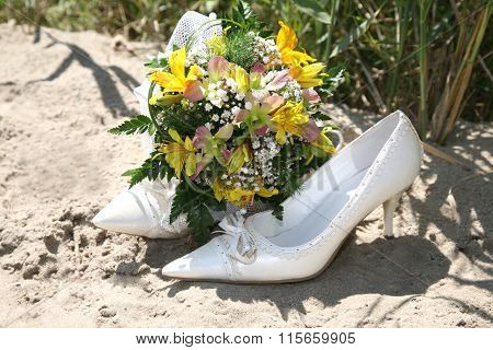 Wedding Bouquet Lies On The Bride's Shoes On The Sand