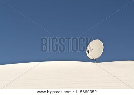 Sattelite Antenna On Snowy Roof.