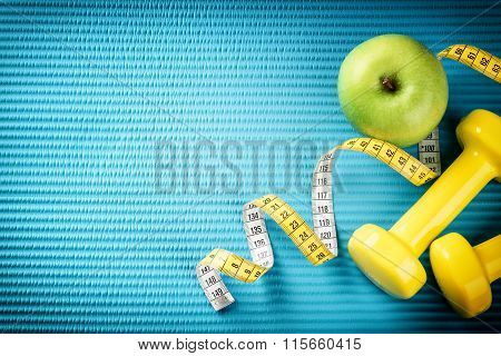 Fitness Background With Dumbbells, Measuring Tape And Apple. Healthy Lifestyle Concept