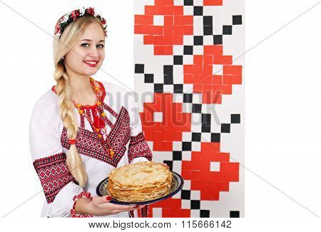 woman in national costume holding a plate of pancakes