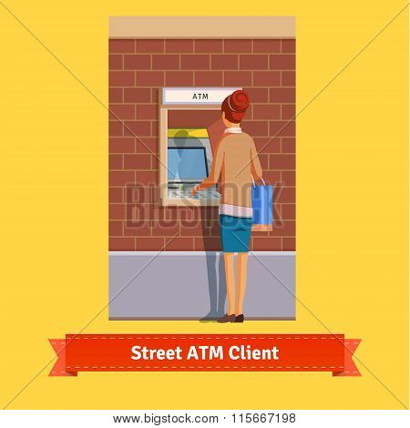 Girl at ATM machine doing deposit or withdrawal