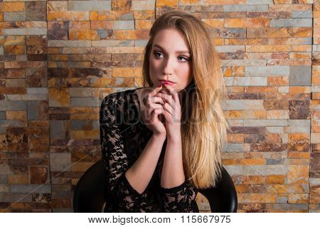 Beautiful young girl in black lace shirt on brick background, holding hand on chin, listening, looki