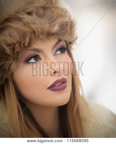 Attractive young Caucasian adult with brown fur cap. Beautiful blonde girl with gorgeous lips
