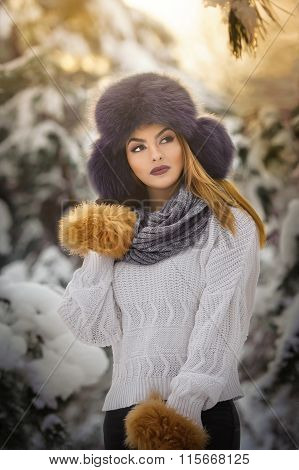 Beautiful woman in white pullover with over-sized fur cap enjoying the winter scenery in forest