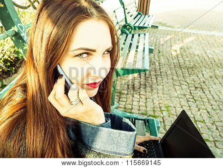 Young beautiful woman with smartphone sitting on a bench