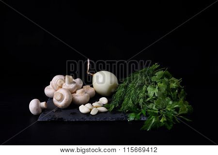 Young spring vegetables on slate board, black background. Champignons, dill, garlic, onion.