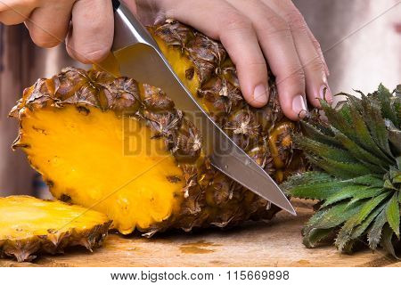 Hands Cutting Pineapple On A Cutting Board