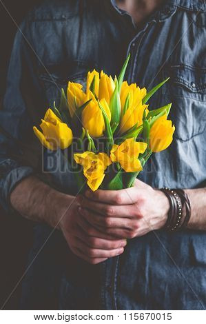 Man holding bouquet of yellow tulips. Gift for a woman