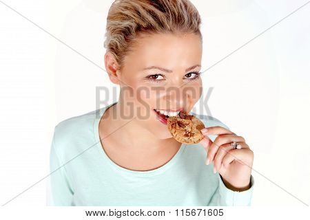Young blonde woman eating cookie
