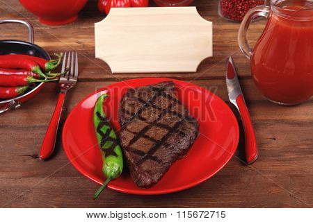red theme lunch : fresh grilled bbq roast beef steak red plate green tomato soup ketchup sauce paprika small glass ground pepper american peppercorn modern cutlery served wooden table empty nameplate