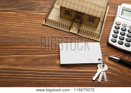 Real Estate Concept. Model house, keys, blank business card, pen and calculator on wooden table. Top