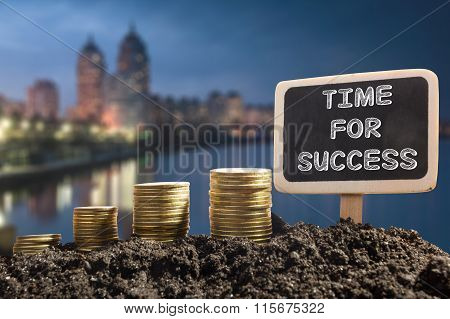 Time for success - Financial opportunity concept. Golden coins in soil Chalkboard on blurred urban b