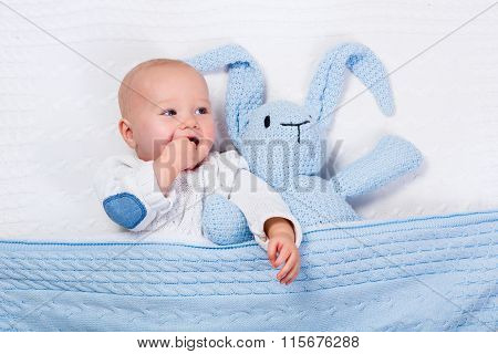 Baby Boy Playing With Blue Knitted Bunny Toy