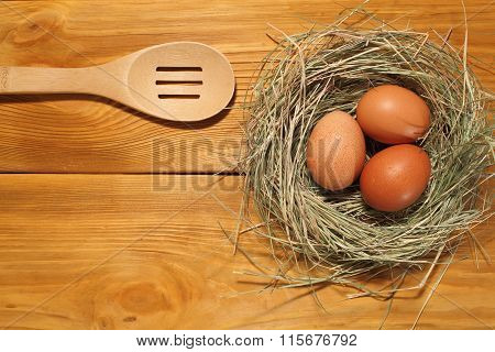 The Composition Of Three Chicken Eggs In A Nest From Grass And Wooden Spoon Lying On A Panel Of Vint