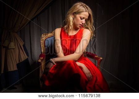 Woman in red dress sitting in chair  and looking away