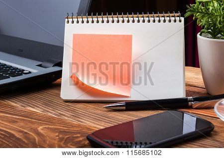 Home workplace with computer, blank notepad, copy space close up
