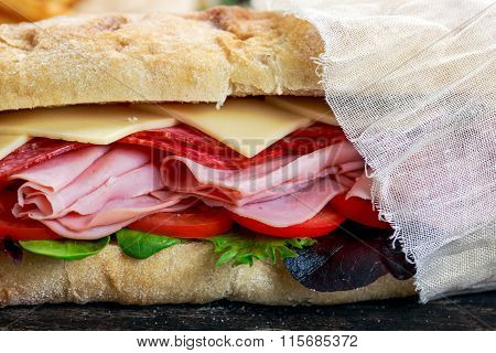 Sandwich with lettuce, slices of  tomatoes, salami, hum and cheese.