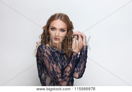Young adorable blonde woman with curly hairstyle in blue dress and necklace touching her hair posing