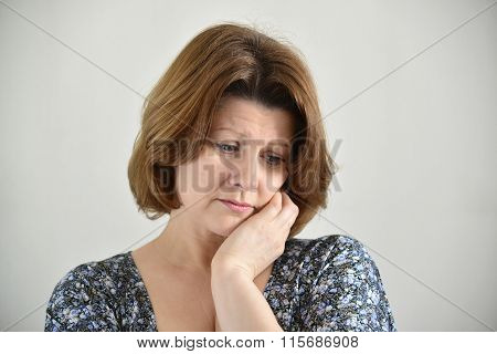Portrait of adult sad female on light background