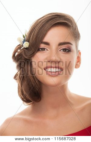 Closeup studio portrait of smiling young adorable brunette woman with low bun hairstyle flower headp