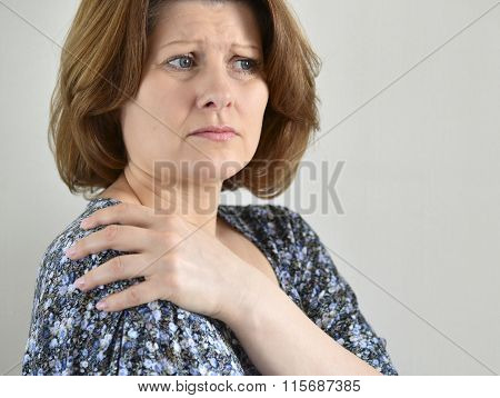 Woman with pain in his shoulder on light background