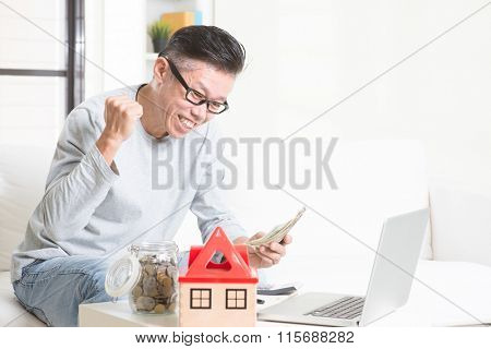 Portrait of happy 50s mature Asian man counting on money and smiling. Saving, retirement, retirees financial planning concept. Family living lifestyle at home.