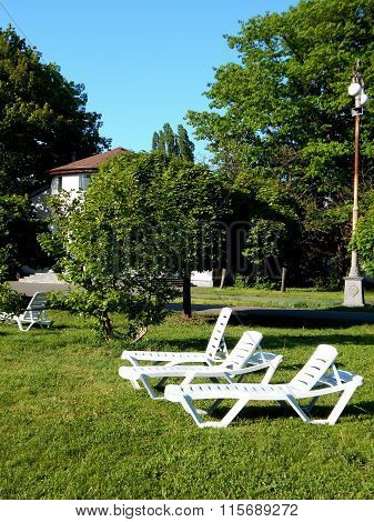 Outdoor furniture on green grass in front of country cottage