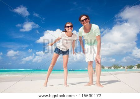Closeup of happy young caucasian couple in sunglasses smiling on beach