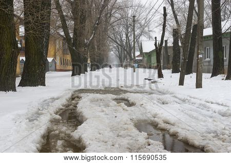 Street with big puddle in suburb of the Dnepropetrovsk city at snowy winter