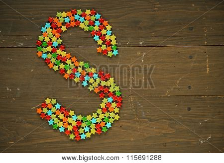 Letter S from alphabet made with star shape candy on a wooden background