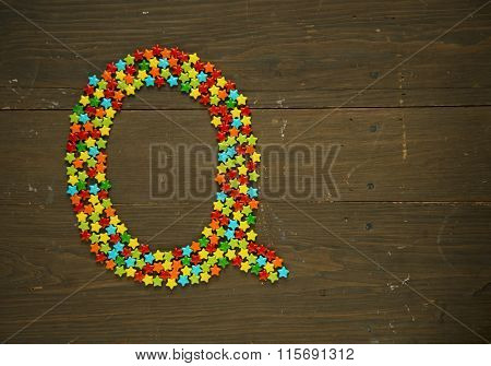 Letter Q from alphabet made with star shape candy on a wooden background