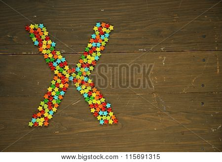 Letter X from alphabet made with star shape candy on a wooden background