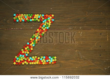 Letter Z from alphabet made with star shape candy on a wooden background