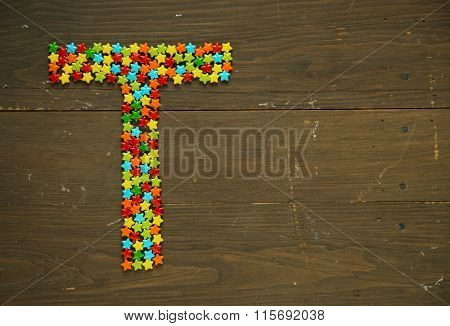 Letter T from alphabet made with star shape candy on a wooden background