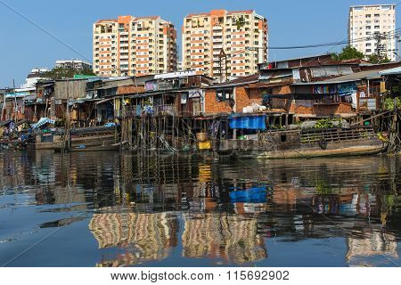 Views of the Slums and new houses, from the river with reflection at water. Vietnam.