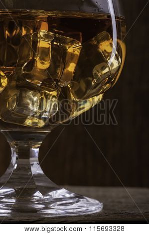 glass of cognac with ice closeup  on cloth background