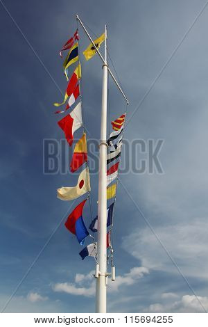 Few Flags On White Pole At Blue Cloudy Sky