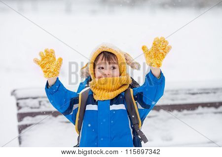 Cute Little Boy, Catching Snowflakes In The Park On A Winter Day