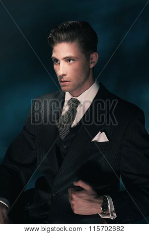 Vintage Fashion Dandy Man In Suit And Tie Sitting On Chair. Hair Combed Back. Dark Blue Background.
