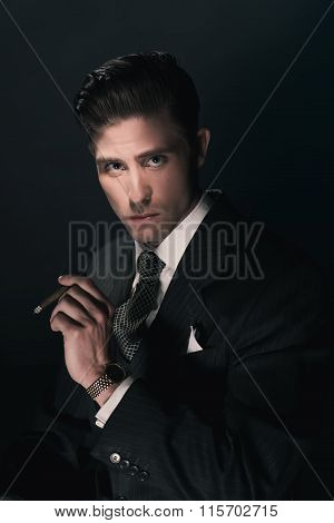 Cigar Smoking Vintage Businessman In Suit And Tie. Hair Combed Back. Against Dark Blue Background.